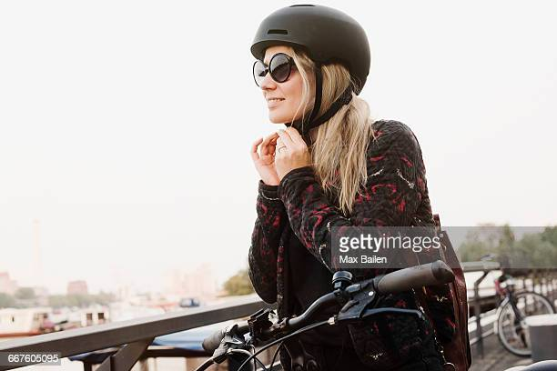 young woman outdoors, putting on helmet, ready to ride bicycle - cycling helmet stock pictures, royalty-free photos & images