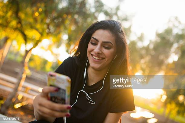 Young woman, outdoors, wearing earphones, holding smartphone