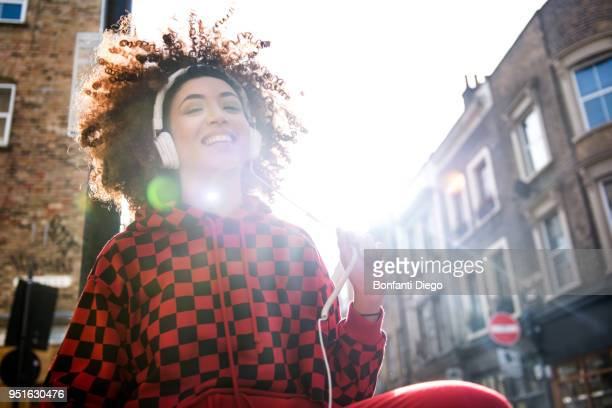 young woman, outdoors, wearing headphone, smiling - hoodie headphones stock pictures, royalty-free photos & images