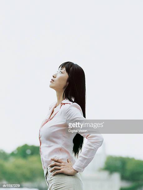 Young Woman Outdoors With Her Arms Akimbo Looking Upwards