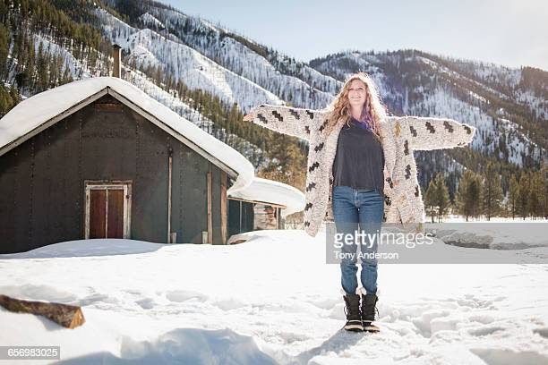 Young woman outside mountain cabin in winter