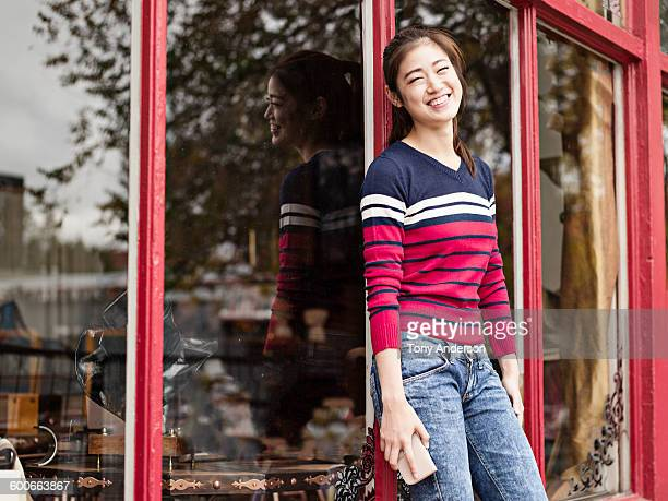 young woman outside shop window - leanincollection stock pictures, royalty-free photos & images