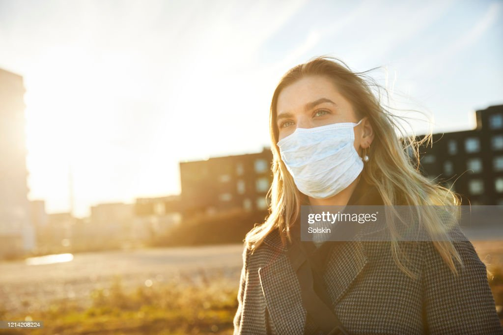 Young woman outside wearing a virus protective face mask : Stockfoto