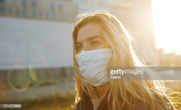 young woman outside wearing a virus protective face mask - covid-19 ストックフォトと画像