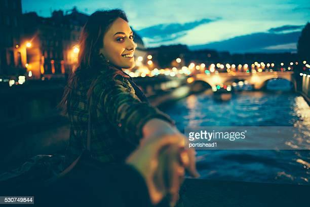 Young woman outstretching hands on river bridge by night