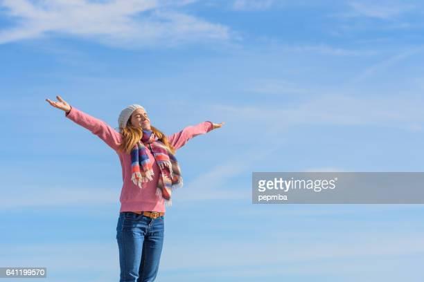 Jonge vrouw over pier met open armen