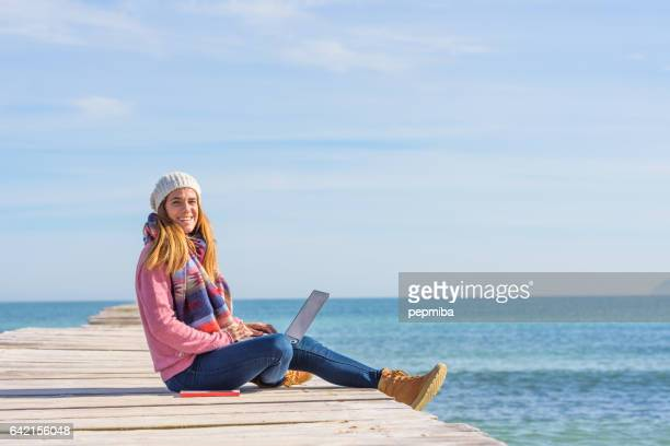 young woman over pier working with her laptop - beauty in nature stock pictures, royalty-free photos & images
