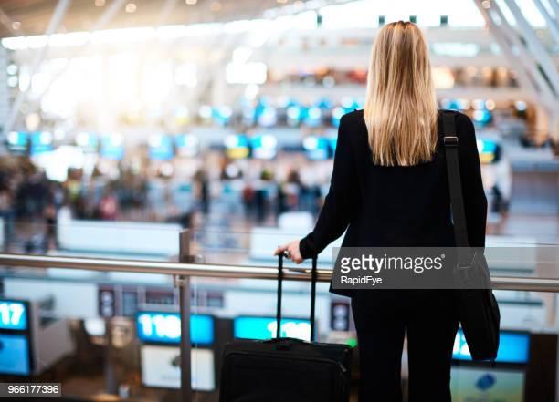 Jonge vrouw met uitzicht op inchecken concourse op luchthaven