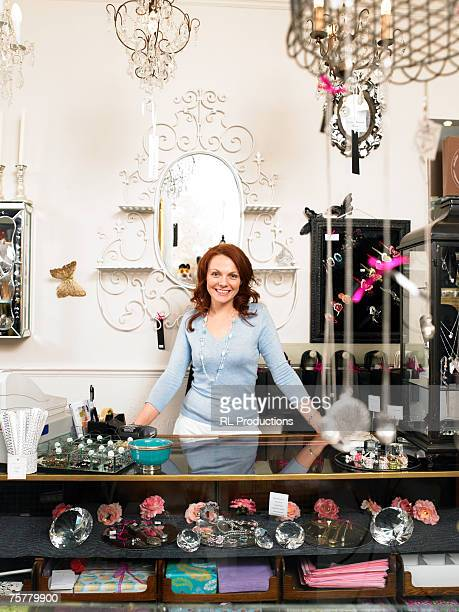 Young woman, owner of gift shop, standing behing counter, smiling, portrait