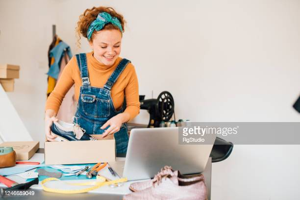 young woman packing and selling leather shoes - leather shoe stock pictures, royalty-free photos & images