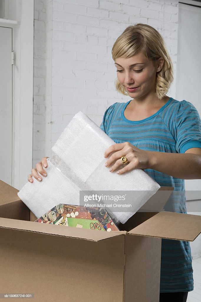Young woman packing box, smiling : Stock Photo