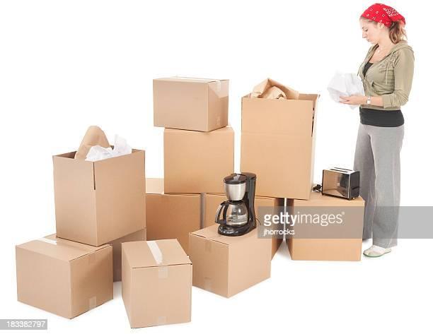 Jeune femme emballage de boîtes de carton de mouvement