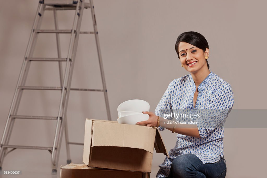 Young woman packing crockery : Stock Photo