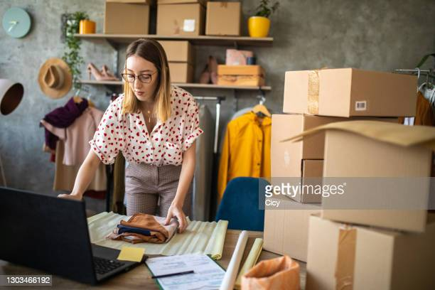 young woman packing scarf in wrapping paper in her online shop office - womenswear stock pictures, royalty-free photos & images