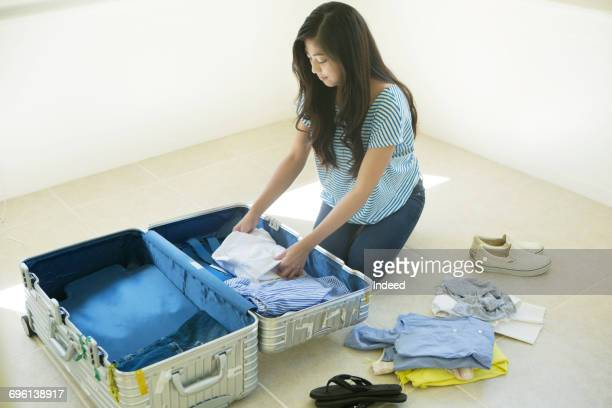 Young woman packing suitcase on floor
