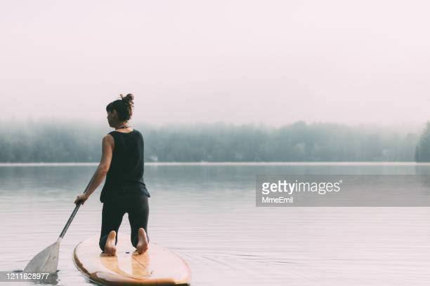 young woman paddleboarding on a calm lake - mmeemil stock pictures, royalty-free photos & images