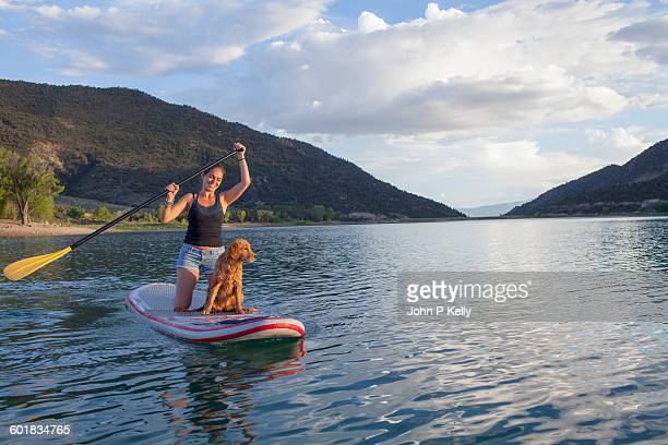 Young woman paddleboarding with puppy on a lake