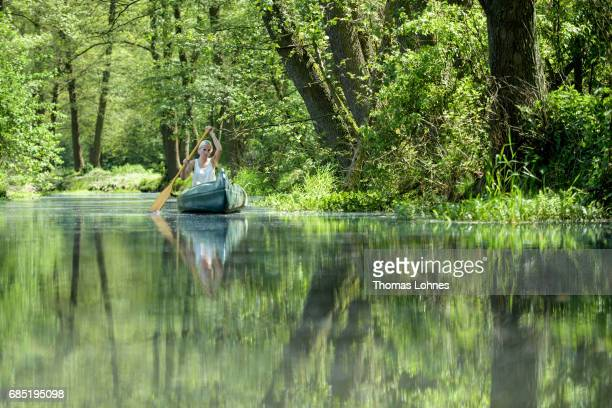 A young woman paddles a canoe on the creek 'Loecknitz' in Brandenburg state on May 19 2017 near Erkner Germany Brandenburg with its multitude of...