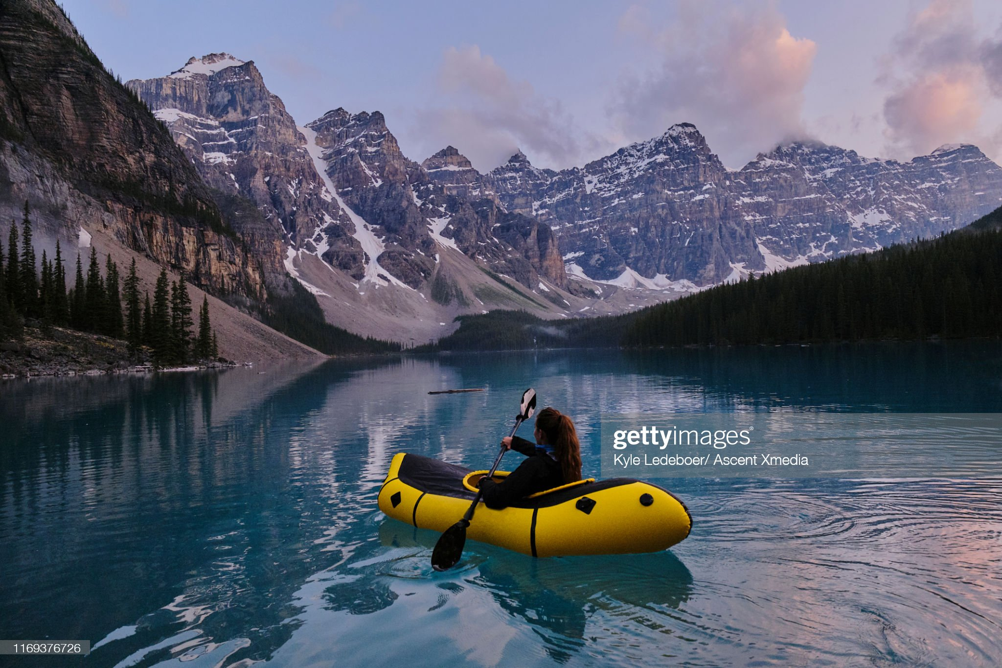Young woman paddles inflatable raft on a calm lake : Stock Photo