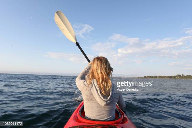 young woman paddles kayak in the morning - vancouver canada stock pictures, royalty-free photos & images