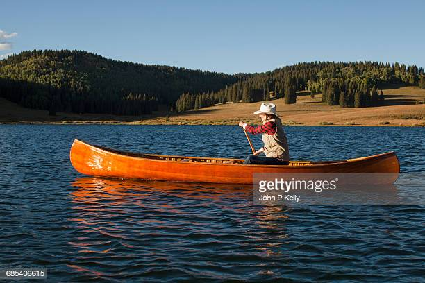 Young woman paddles vintage wooden canoe on a lake