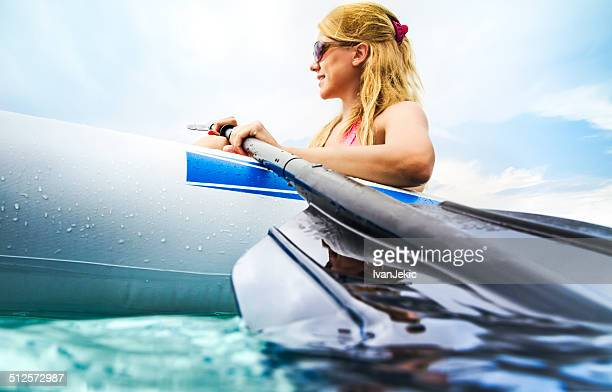 Young woman paddling in kayak on sea