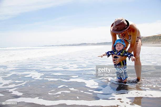 Young woman paddling in sea with baby son