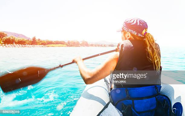 young woman paddling kayak on sunny day at sea - sea kayaking stock pictures, royalty-free photos & images