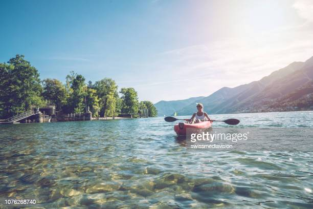 young woman paddling red canoe on mountain lake - switzerland stock pictures, royalty-free photos & images