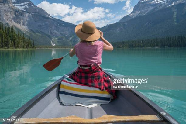 young woman paddling red canoe on turquoise lake - canadian culture stock pictures, royalty-free photos & images