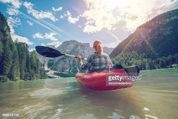 young woman paddling red canoe on turquoise lake - pragser wildsee stock pictures, royalty-free photos & images