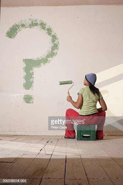 Young woman painted big question mark on wall