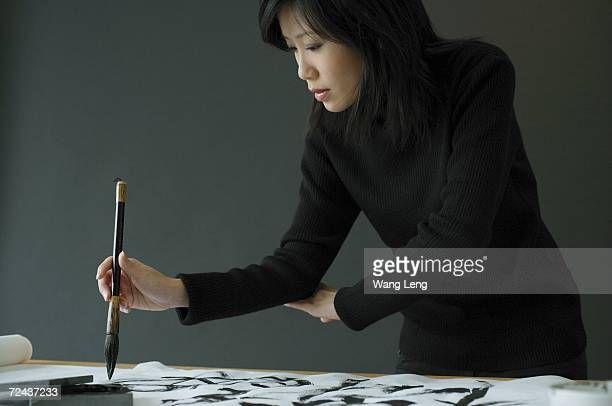 Young woman painting Chinese calligraphy