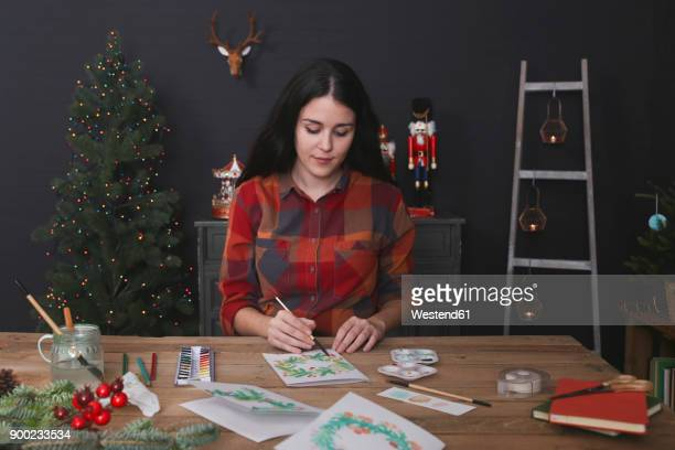 Young woman painting Christmas card with water colors