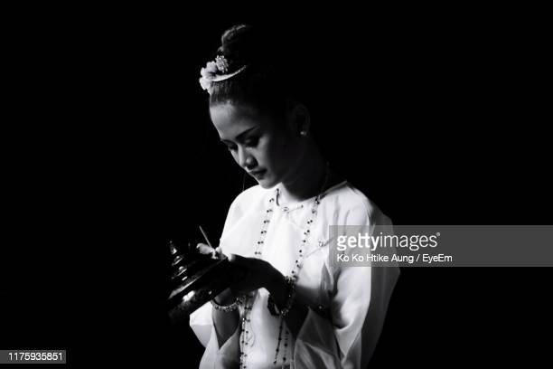 young woman painting decoration while standing against black background - ko ko htike aung stock pictures, royalty-free photos & images