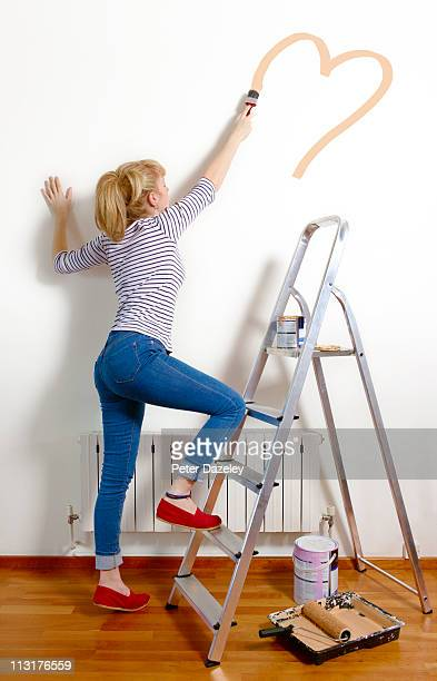 Young woman painting heart on wall of new home