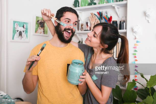 Young woman painting her boyfriends face with paintbrush