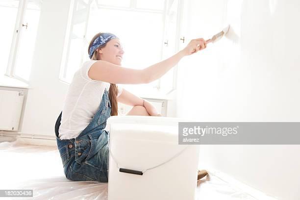 junge frau painting ihren house - renovierung themengebiet stock-fotos und bilder