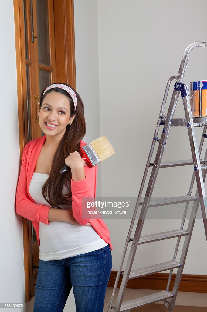Young woman painting her house : Stock Photo