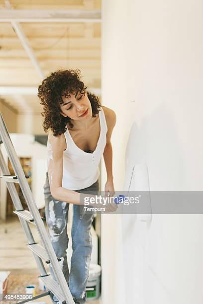 Junge Frau painting Ihr neues apartment.