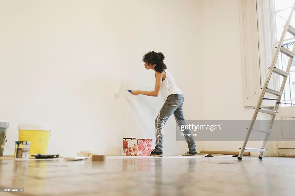 Young woman painting her new apartment. : Stock Photo