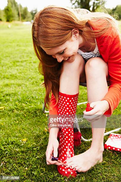 Young woman painting her toenails outside