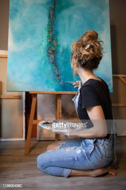 young woman painting in her atelier - pittore foto e immagini stock