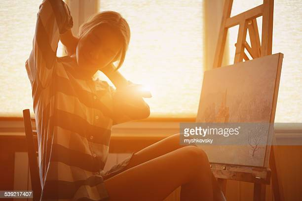 Young woman painting landscape near the window