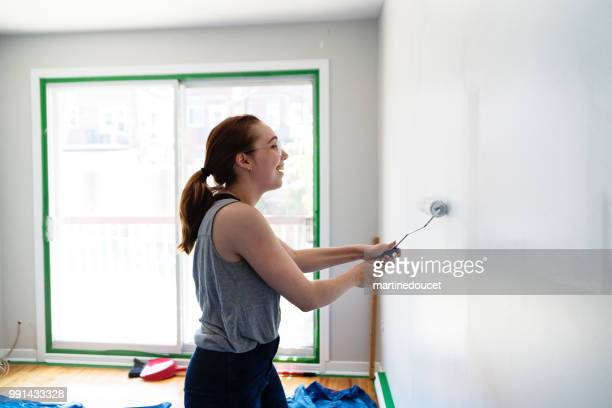 Young woman painting living room in first appartement.