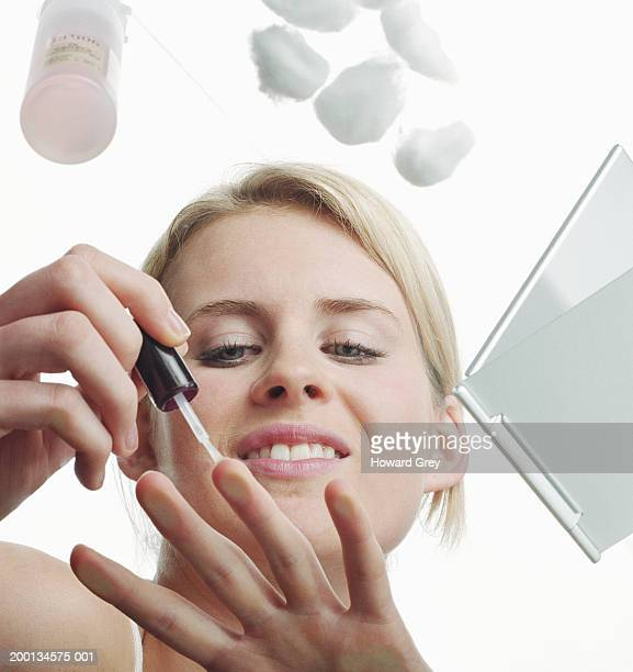 Young woman painting nails, low angle view
