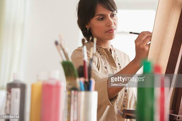 Young woman painting on easel