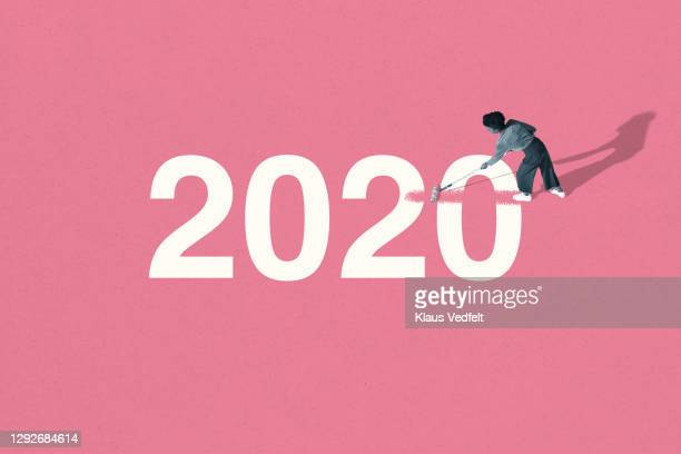 young woman painting over 2020 with pink roller - oresund region stock pictures, royalty-free photos & images