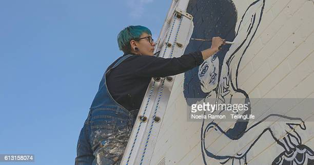 Young woman painting street art at Mornington Peninsula, Victoria, Australia