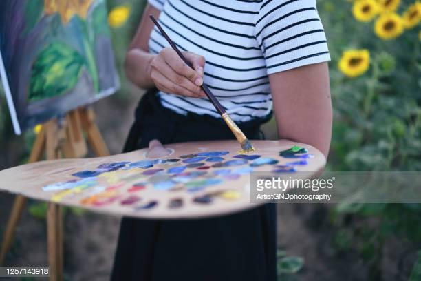junge frau malt sonnenblumen im freien - acrylmalerei stock-fotos und bilder